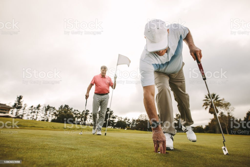 Senior golf player picking golf ball out of hole with second player...