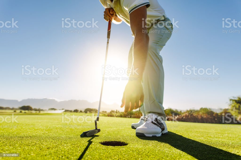 Golfer picking the ball from hole after put stock photo