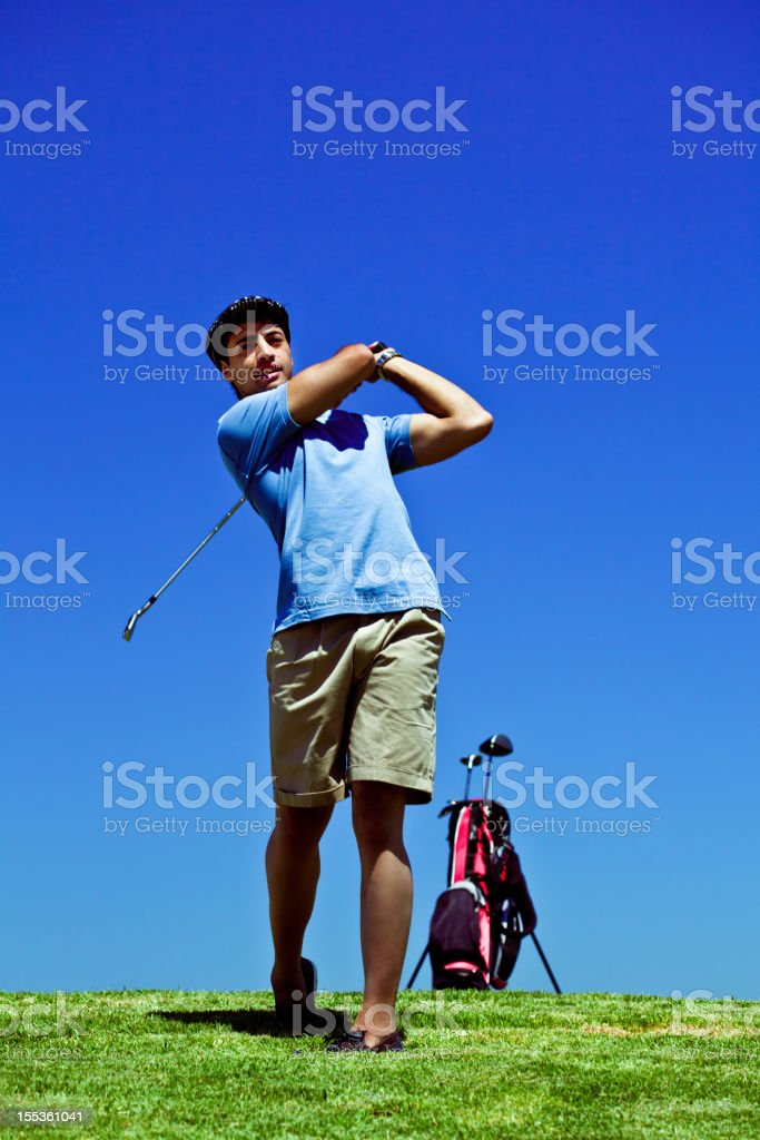 Golfer Young adult golfer swinging against clear blue sky. 25-29 Years Stock Photo