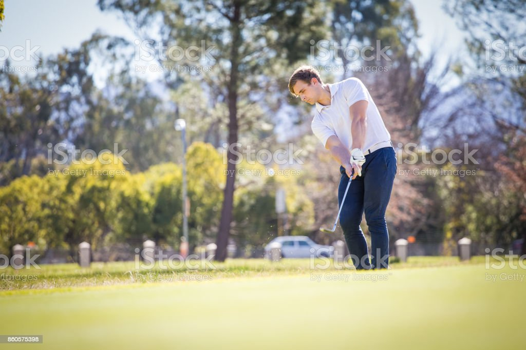 Golfer playing a chip shot on a golf course in South Africa stock photo