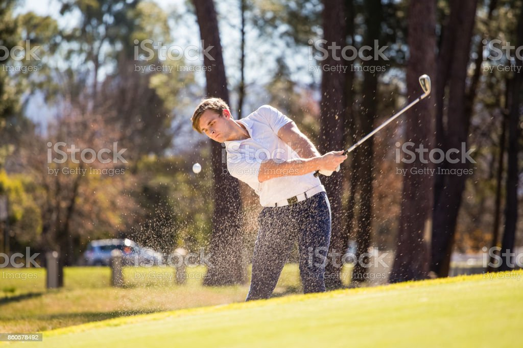 Golfer playing a chip shot onto a green on a golf course in South Africa stock photo