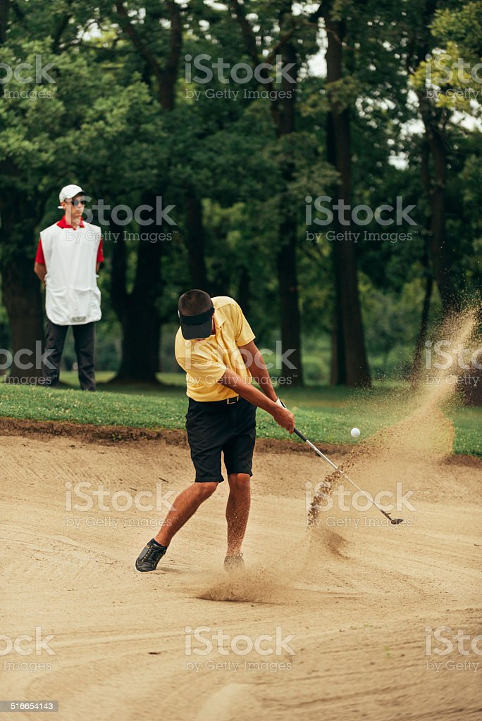 Golfer playing from sand bunker stock photo