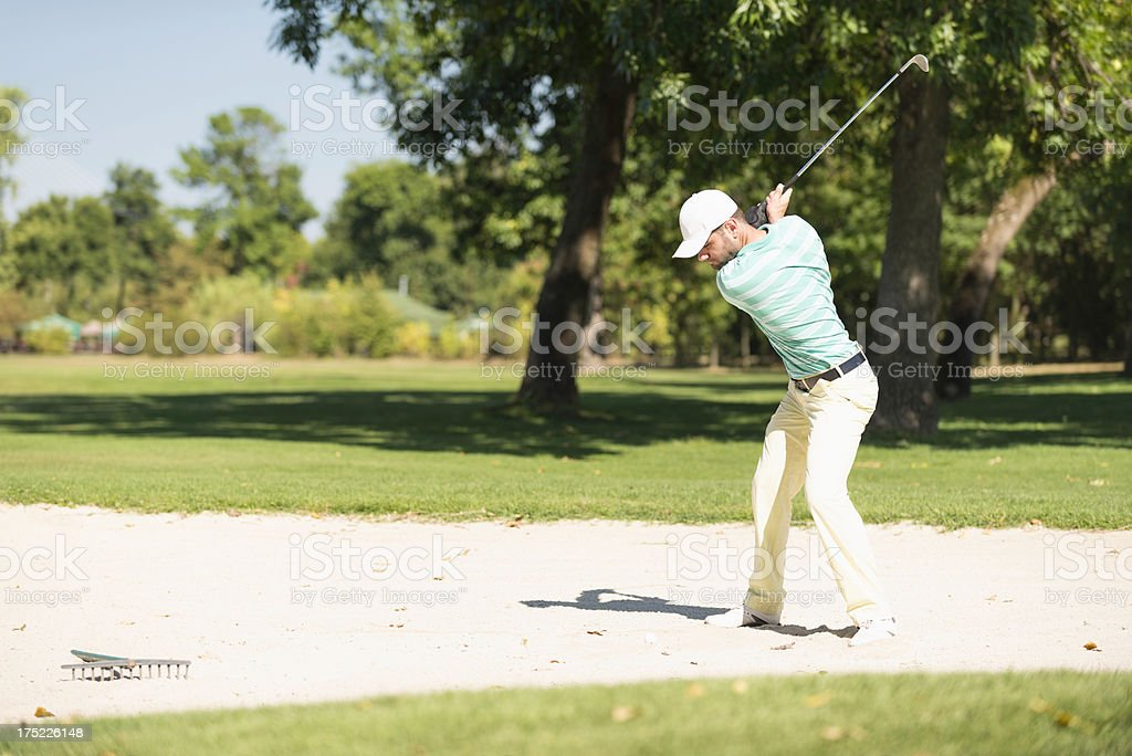 Golfer playing from sand trap royalty-free stock photo