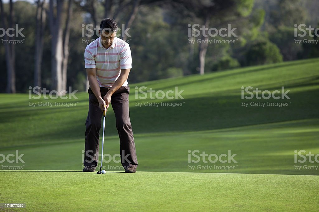 Golfer playing in putting green, ball on the move royalty-free stock photo