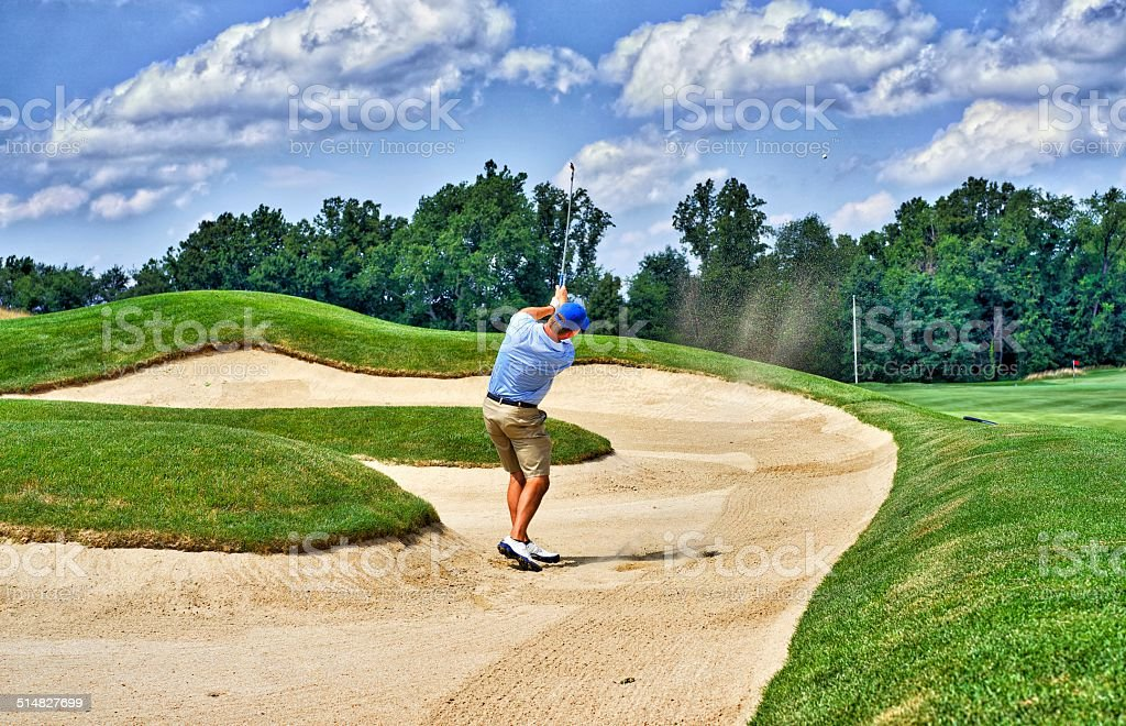 Golfer plays from sand bunker to nearby green stock photo