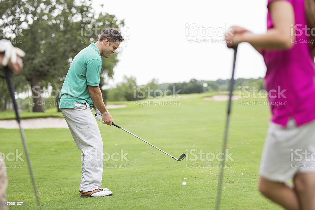 Golfer preparing to tee off while playing golf with family royalty-free stock photo