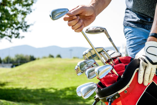 golfer pulling out a golf club from red golf bag - golf clubs stock photos and pictures