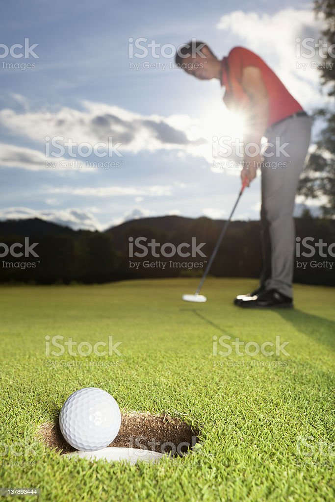 Golfeur de mettre le ballon dans la tasse. - Photo