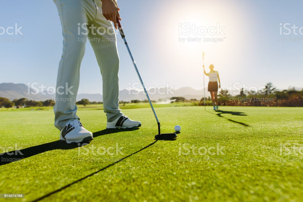 Golfer putting ball with female partner holding flag on golf course - foto de stock