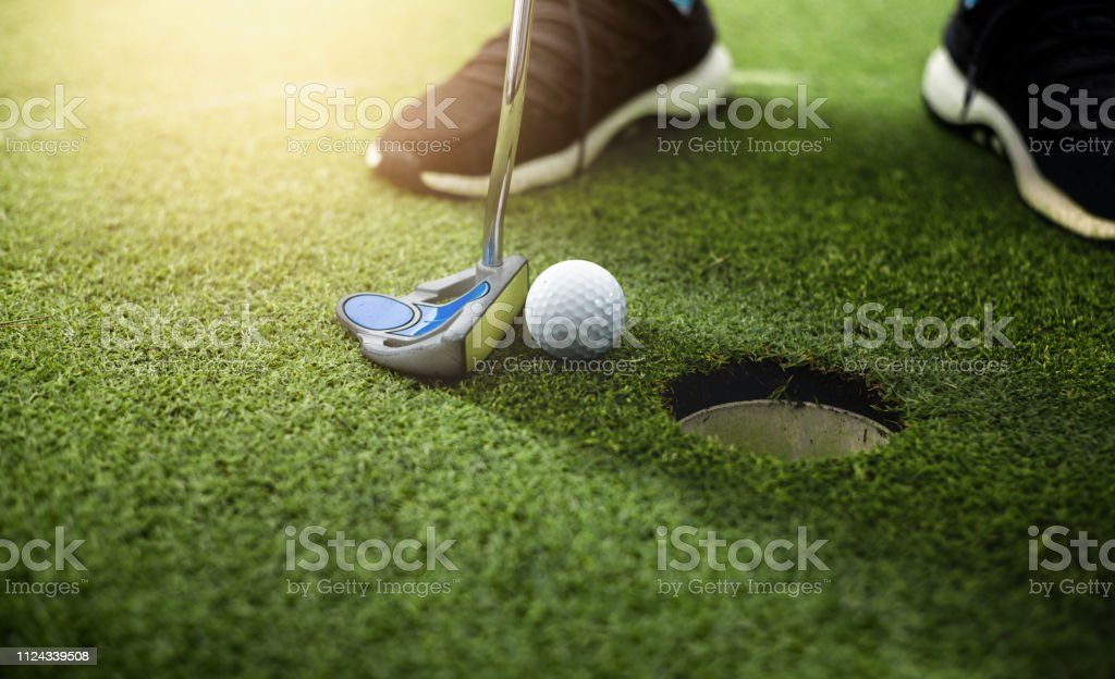 Golfer putting golf ball approach to the golf hole on the green...