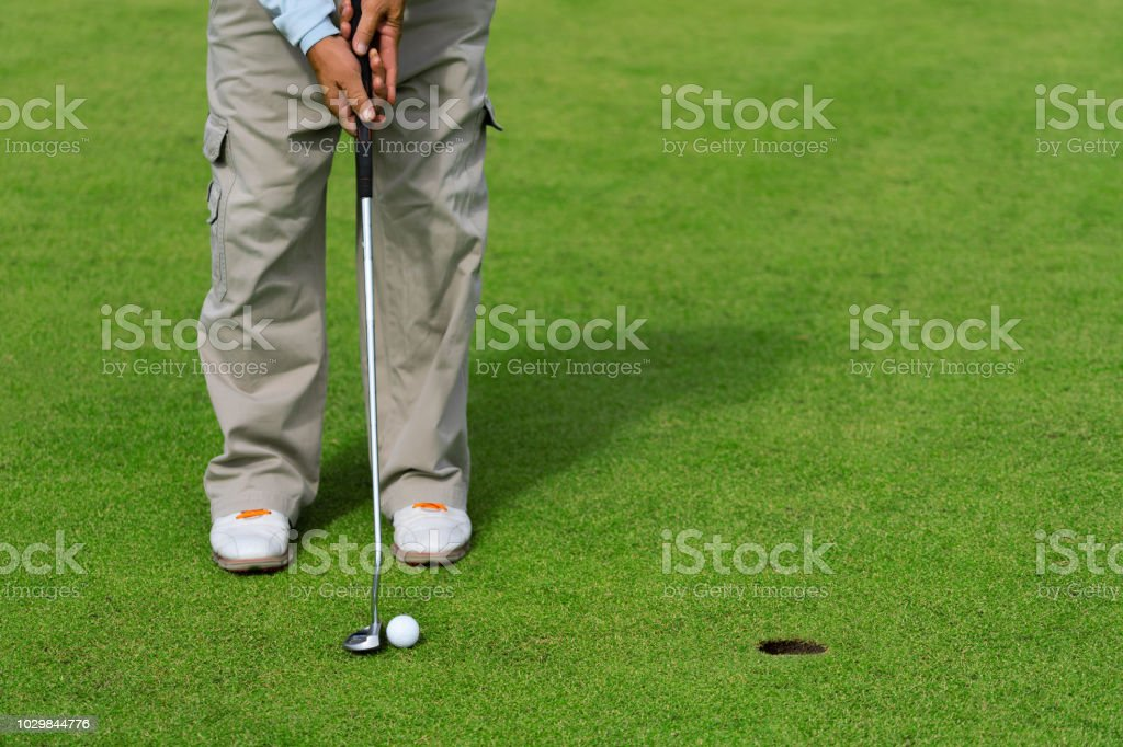 Golfer putting golf ball on the green golf, lens flare on sun set...