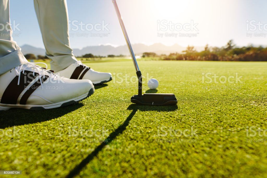 Golfer putting golf ball to hole stock photo