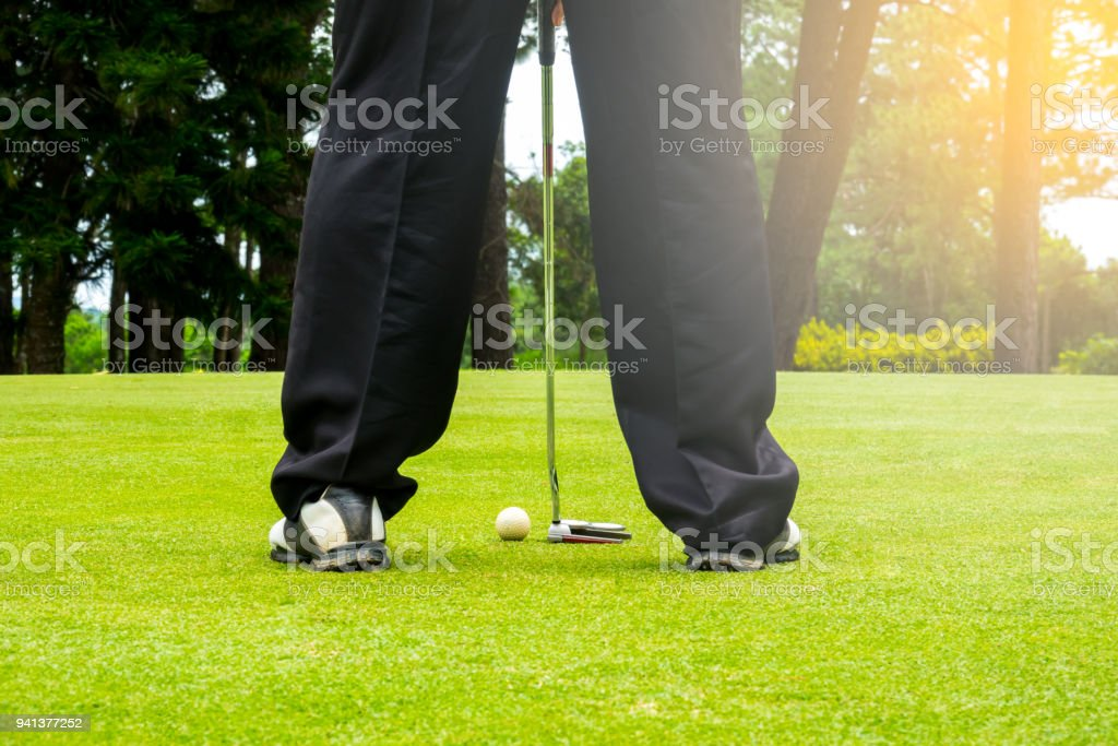 Golfer putting golf ball to hole to the winner