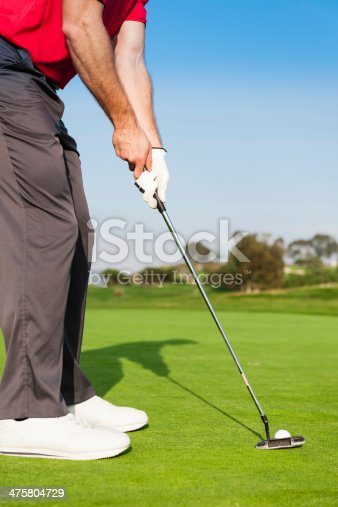 A golfer in a red shirt putting  the ball in the hole.  http://blog.michaelsvoboda.com/GolfBanner.jpg