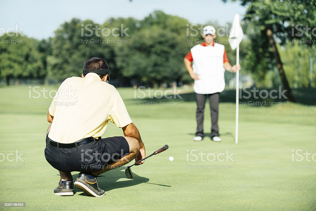 Golfer reading green stock photo