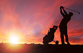 Silhouette of golfer and golf bag by his side swinging club toward sunset with deliberate lens flare and copy space. Sunset background image shot in Calgary (see attached). Silhouette created/drawn in Photoshop.  Sun and flare added using Photoshop filter renders.
