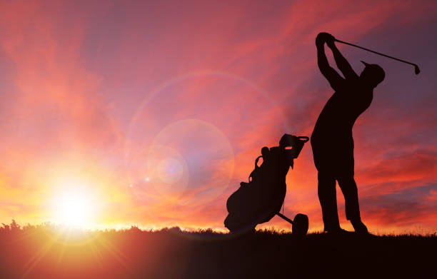 Golfer Silhouette During Sunset With Copy Space Silhouette of golfer and golf bag by his side swinging club toward sunset with deliberate lens flare and copy space. Sunset background image shot in Calgary (see attached). Silhouette created/drawn in Photoshop.  Sun and flare added using Photoshop filter renders. twilight stock pictures, royalty-free photos & images