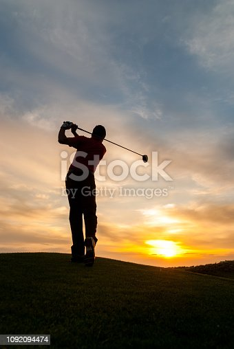 Golfer silhouette with dramatic sky.