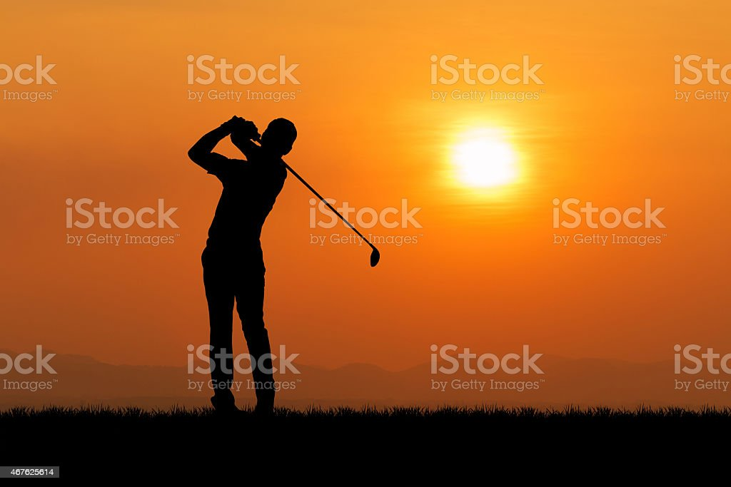 Golfer silhouetted against orange sunset stock photo
