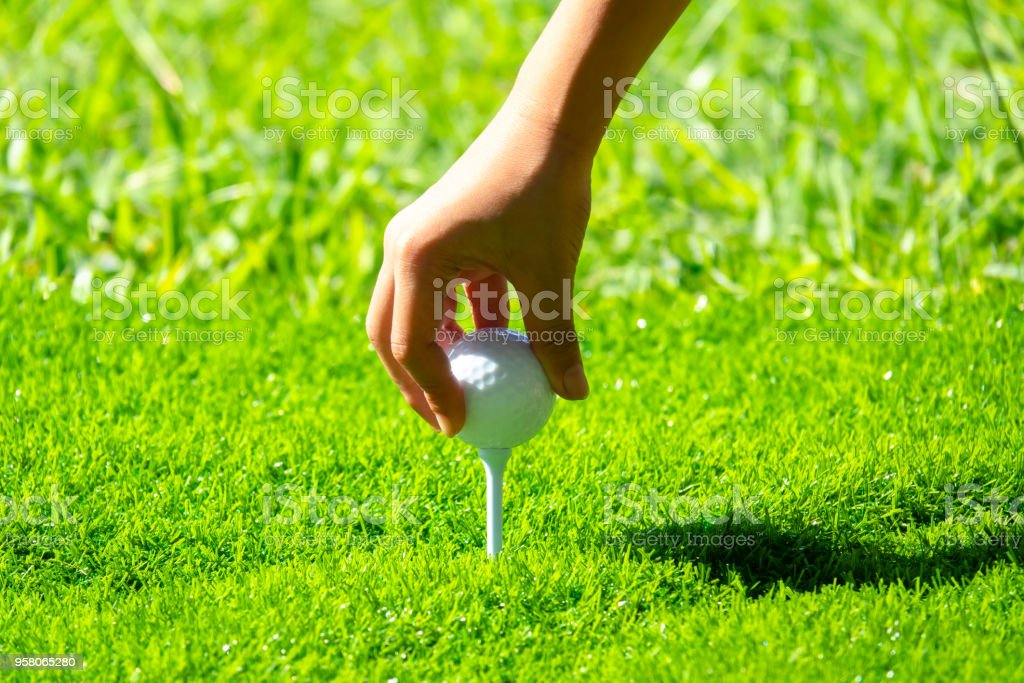 Golfer sitting golf ball on tee for hitting to hole