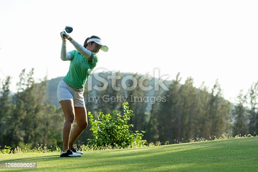 istock Golfer sport approach on course golf ball fairway. People lifestyle woman playing game golf tee of on the green grass background. Asia female player game shot in summer. Healthy and Sport outdoor 1268698657