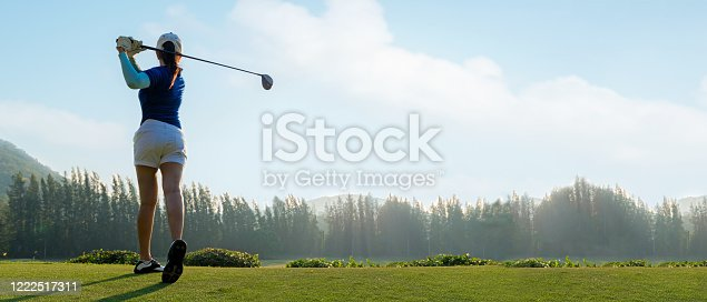 istock Golfer sport course golf ball fairway. People lifestyle woman playing game golf tee of on the green grass sunset background. Asia female player game shot in summer. copy space banner 1222517311