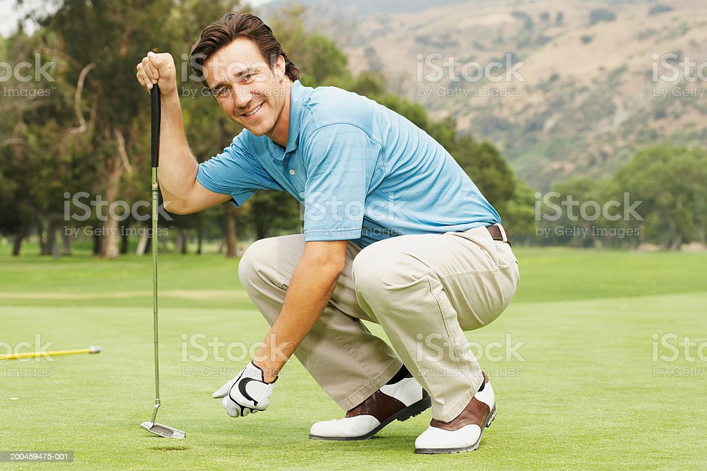 Golfer squatting on green royalty-free stock photo