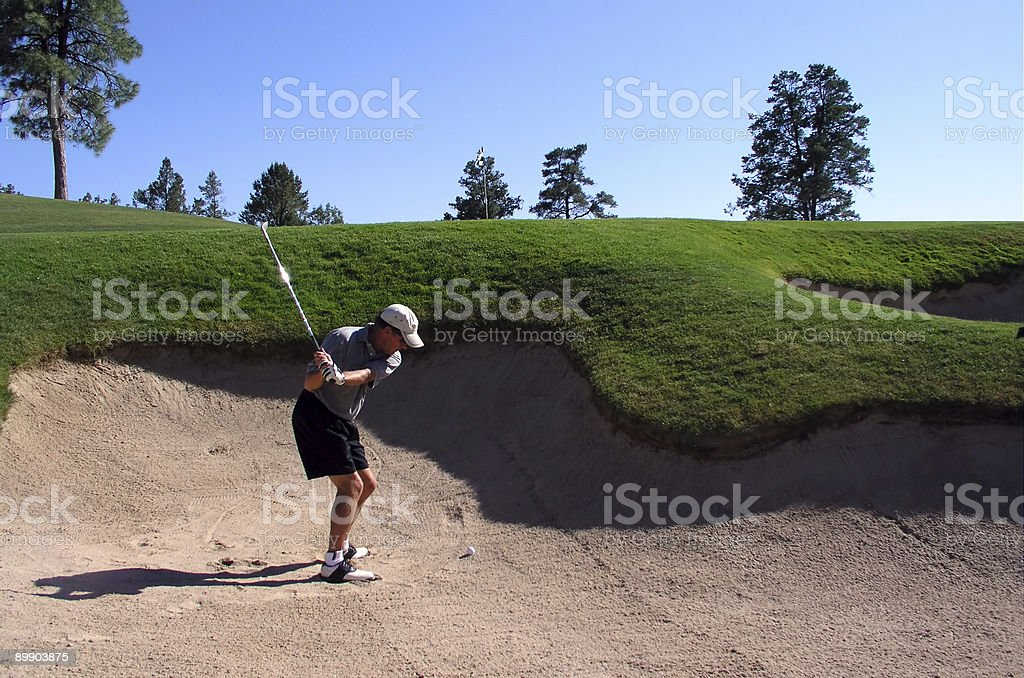 Golfer successfully hitting golf ball out of a sand trap royalty free stockfoto
