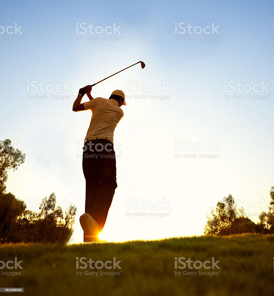 Golfer swinging at beautiful sunset stock photo