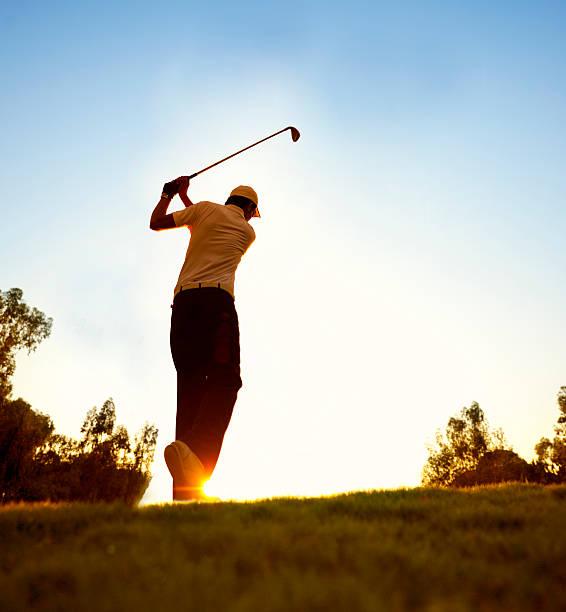 Golfer swinging at beautiful sunset stock photo