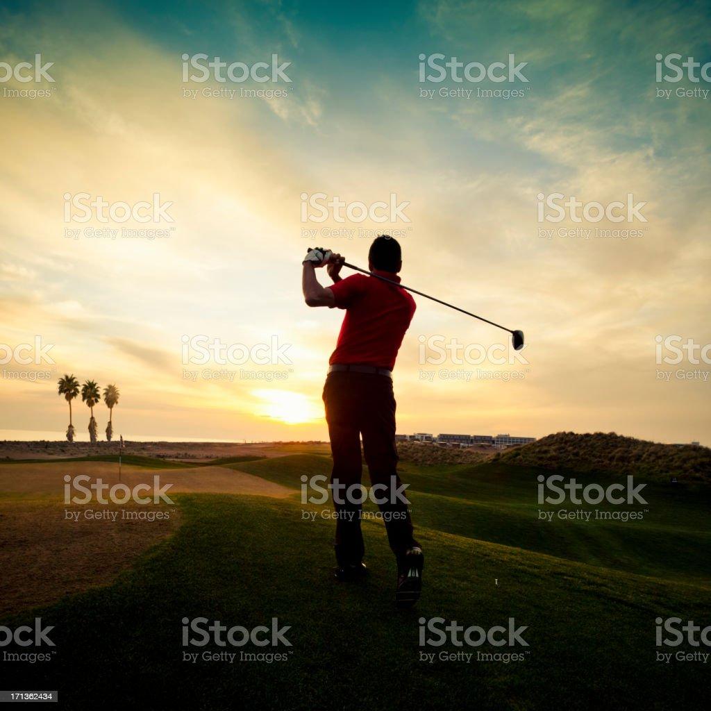 Golfer swinging at sunset royalty-free stock photo