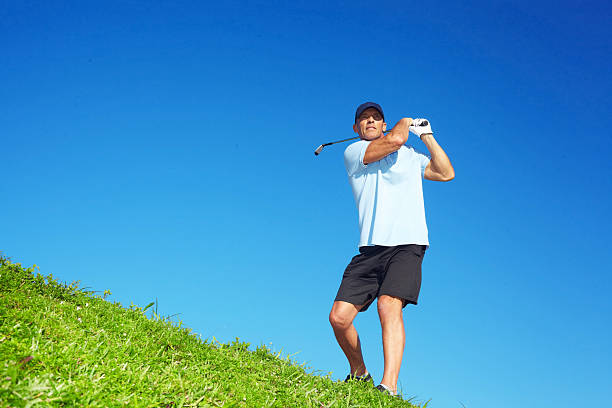 Golfer Swinging Golf Club On Course stock photo