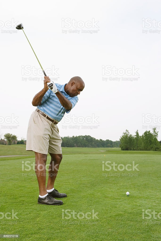 Golfer swinging to hit ball on golf course stock photo