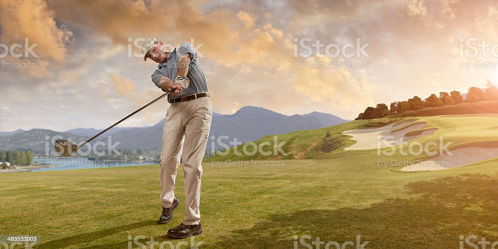 Golfer Swings at Sunset stock photo