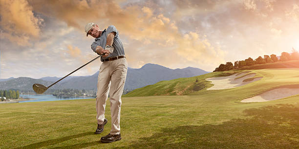 golfer swings at sunset - golf stock photos and pictures