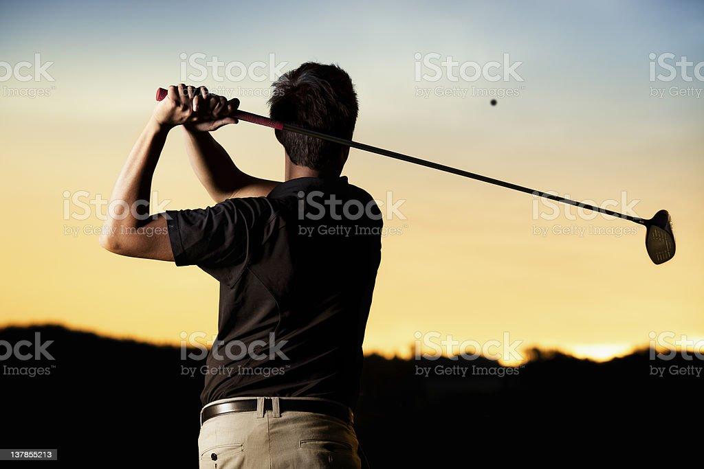 Golfeur pratiquer au coucher du soleil. - Photo