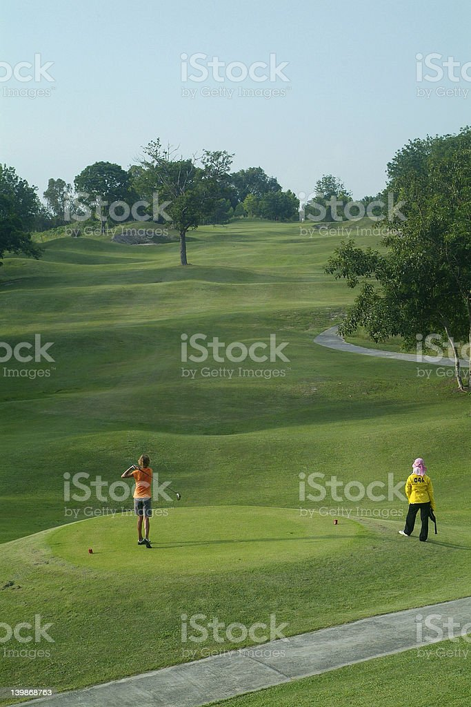 Golfer teeing off stock photo