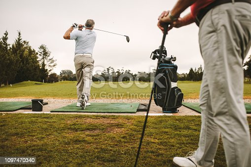 Senior man at a driving range playing golf and practice his swing with other man standing in front. Senior male golfers practicing at golf course.