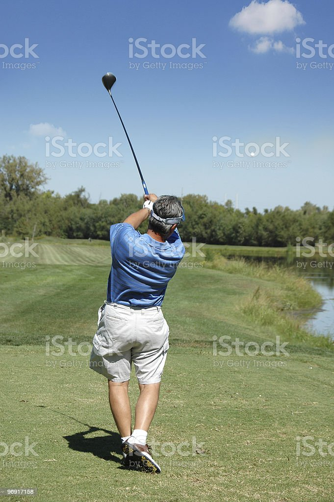 Golfer tees off royalty-free stock photo
