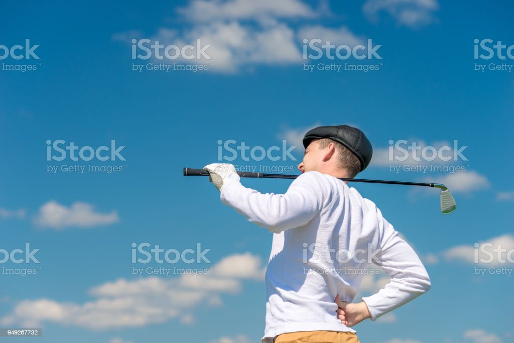 Golfer with a golf club rubs a sick back on the field stock photo