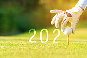 Golfer woman putting golf ball for Happy New Year 2020 on the green golf for new healthy sporty, copy space. Healthy and Holiday Concept.