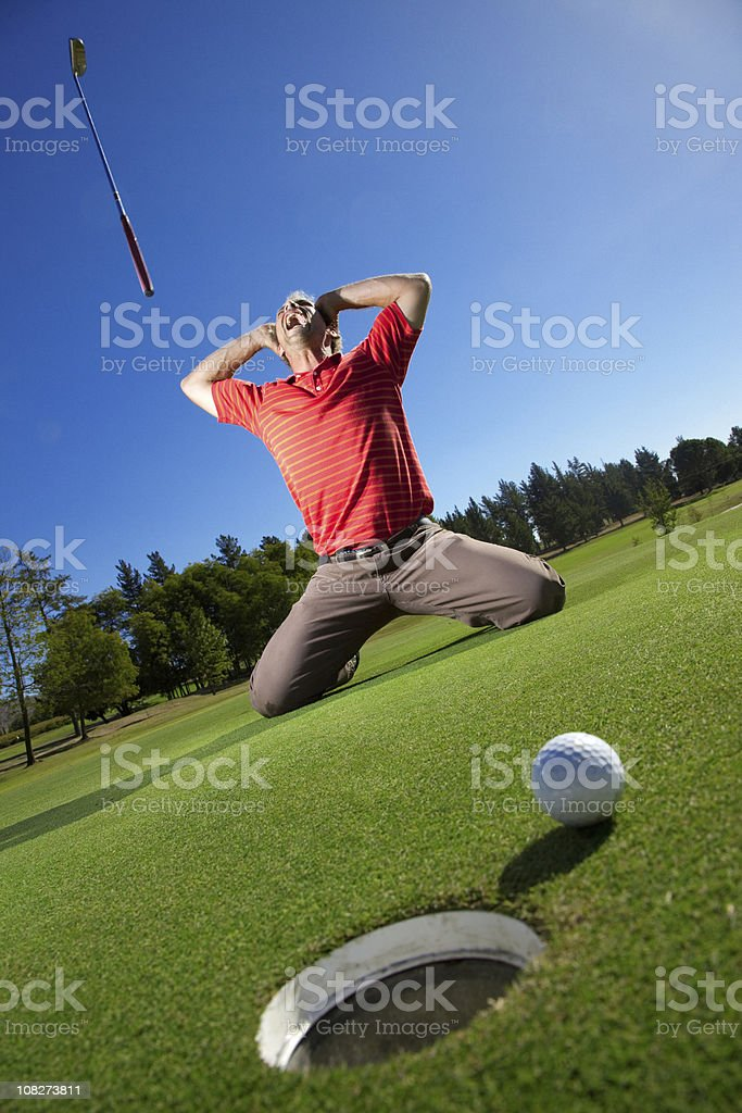 Golfer Yelling and Throwing Golf Club with Ball Beside Hole stock photo