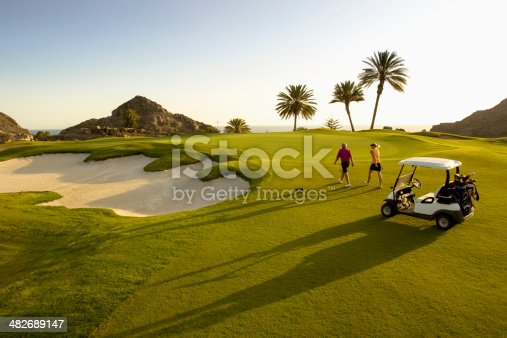 Male and female golfers follow their shots on the golf course putting green.