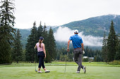Two golfers look down the fairway and discuss the tee shot. Young golfers enjoy playing golf together.