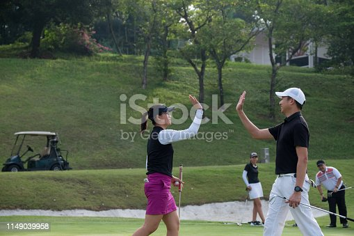 Side view of golfers giving high-five at golf course. Happy coach and teenage girl is celebrating success at playing field. They are wearing sports clothing.