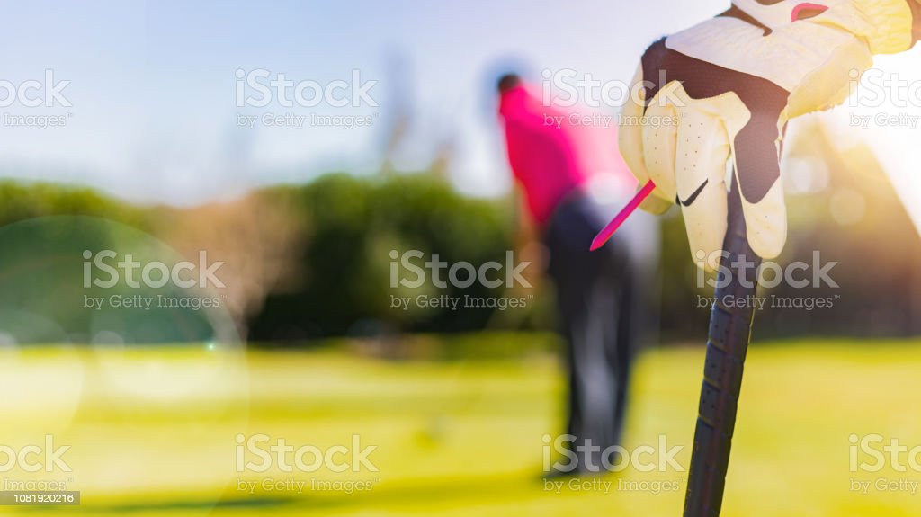 Golfers Hand and Glove leaning on a golf club on a sunny morning