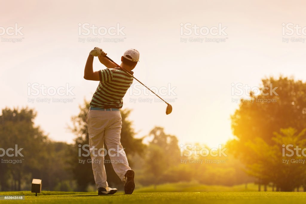 Golfers hit sweeping golf course in the summer stock photo