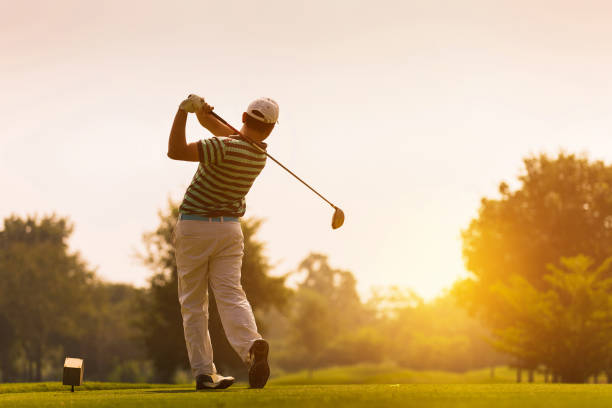 golfers hit sweeping golf course in the summer - golf stock pictures, royalty-free photos & images