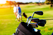 Golfers on golf course with golf bag in-focus in foreground