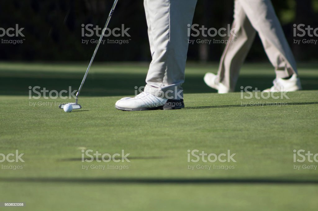 2 golfers legs only putting on golf course green